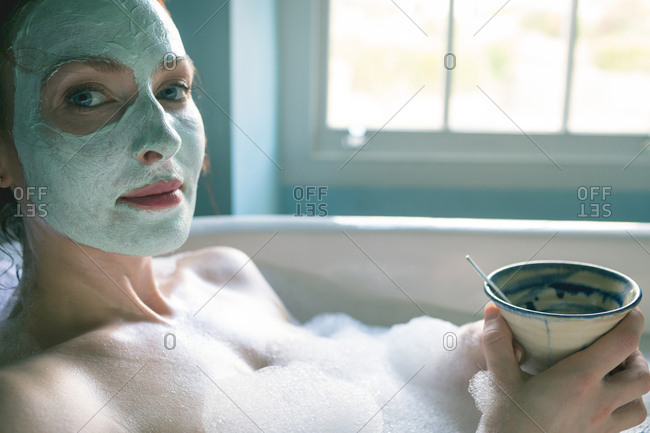 Woman with coffee cup in bathtub at bathroom