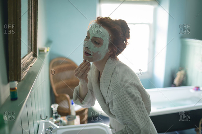 Woman removing facial mask in front of mirror in bathroom at home