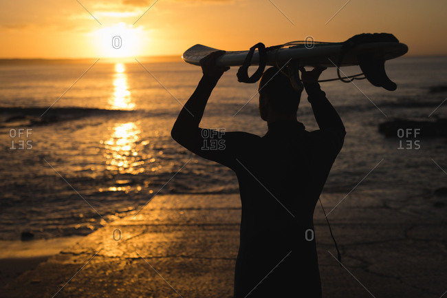 Surfer carrying the surfboard on his head on beach