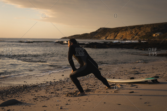 Surfer stretching on beach during sunset