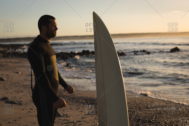 Surfer with surfboard standing on beach during sunset