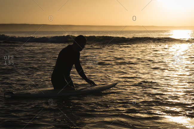 Surfer with surfboard surfing on sea during sunset
