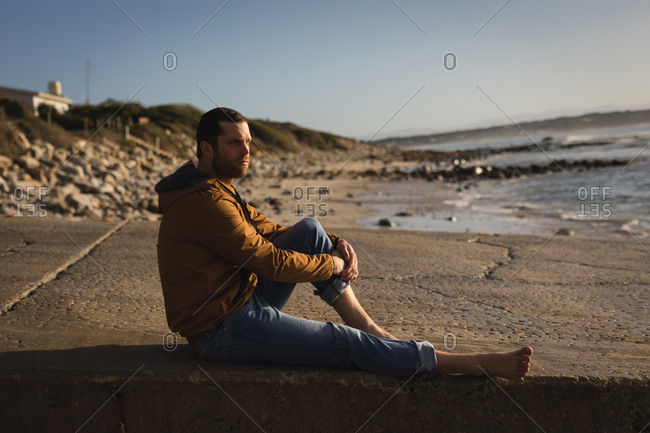 Thoughtful man sitting on promenade near beach