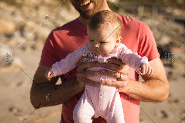Close-up of father holding baby on beach