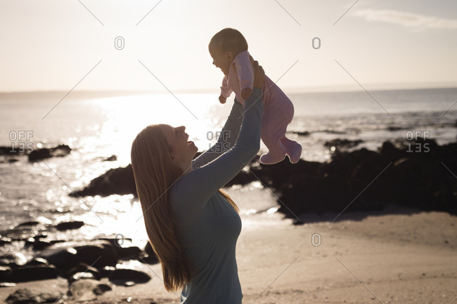 Happy mother playing with baby on beach