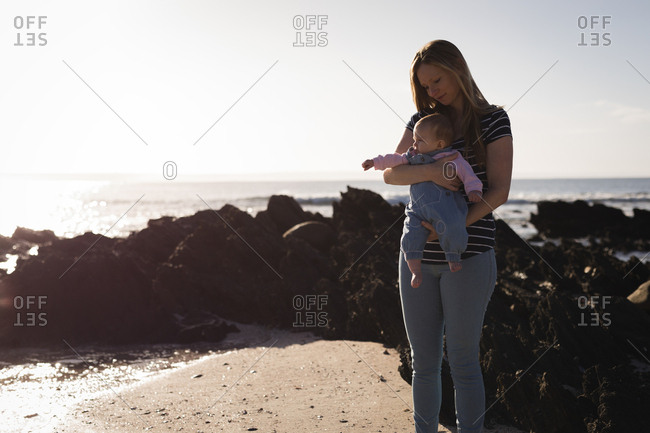 Mother with baby standing at beach on a sunny day