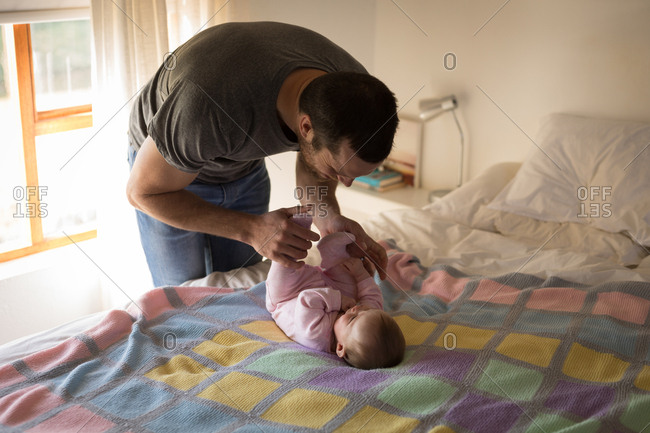 Father having fun with baby on bed at home