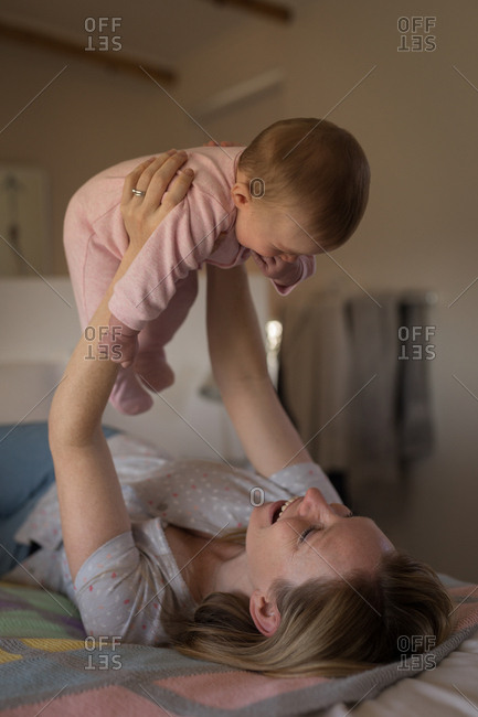 Mother having fun with baby on bed in bedroom at home