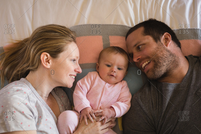 Parents lying with baby on bed in bedroom at home