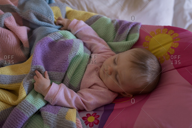 Baby relaxing on bed in bedroom at home