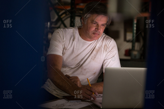 Male mechanic drawing a car model while using laptop in garage