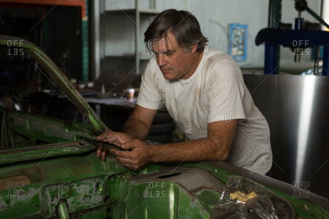 Male mechanic using digital tablet in garage