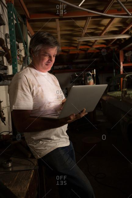 Male mechanic using laptop in garage