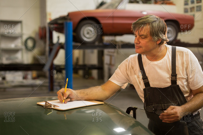 Male mechanic writing on clipboard in garage