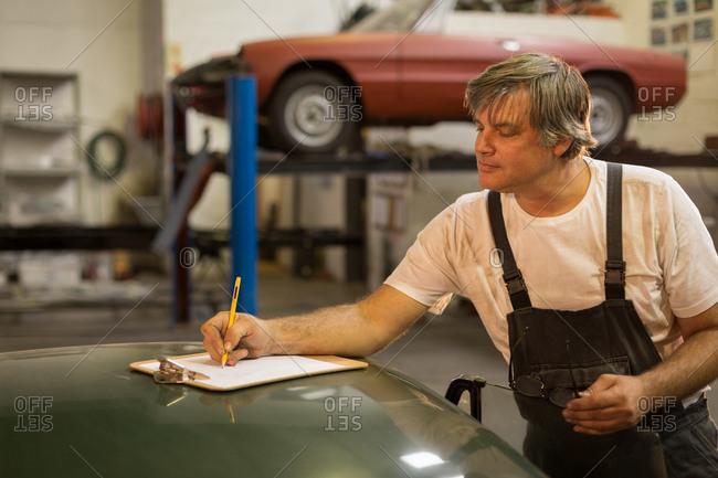 Male mechanic writing on clipboard in garage