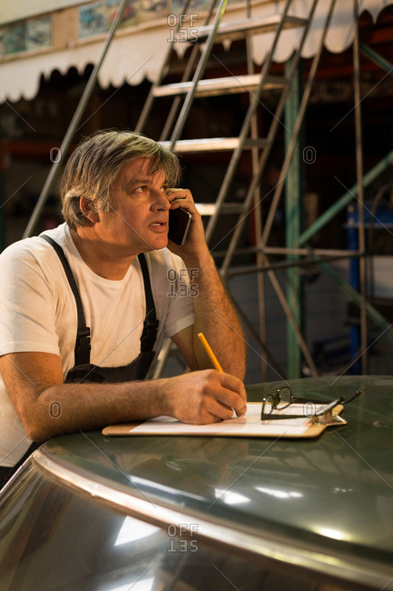 Male mechanic talking on mobile phone while writing on clipboard in garage