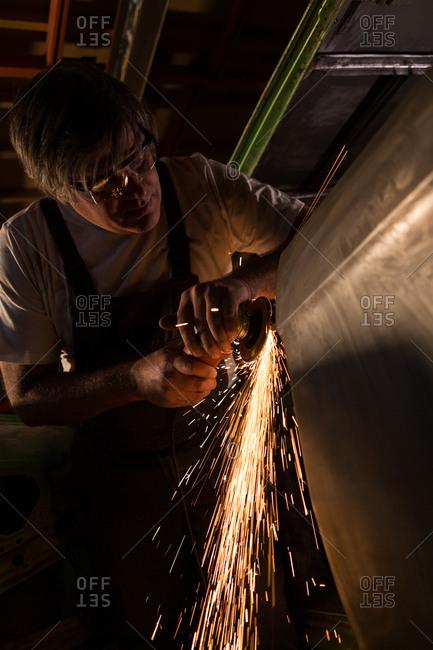 Male mechanic using grinder machine in garage