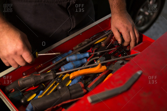 Male mechanic removing tools from drawer in garage