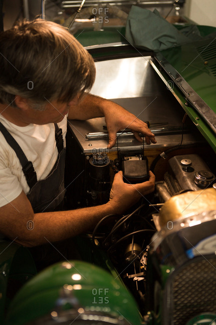 Male mechanic servicing a car in garage