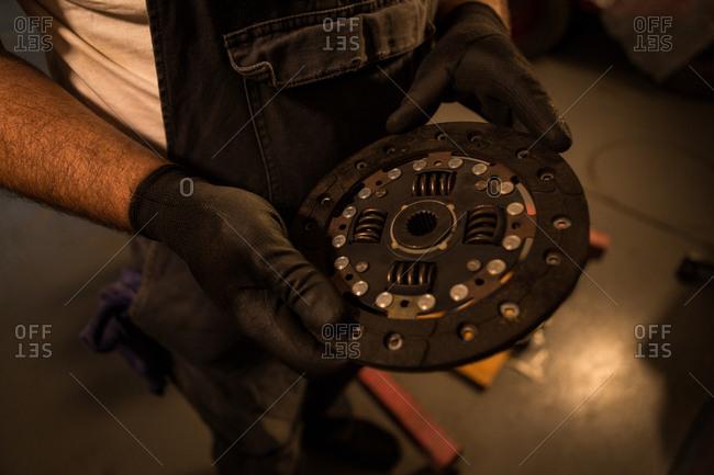 Mid section of male mechanic holding mac wheel