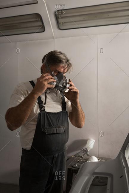 Male mechanic wearing gas mask in garage