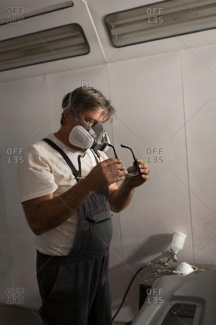 Male mechanic wearing protective eyewear in garage