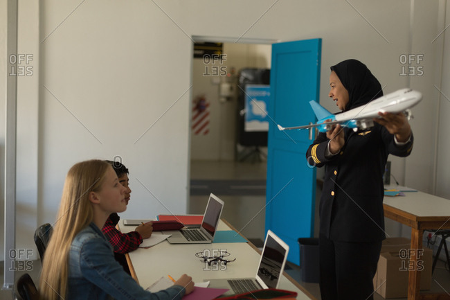 Female pilot teaching about model plane to kids in training institute