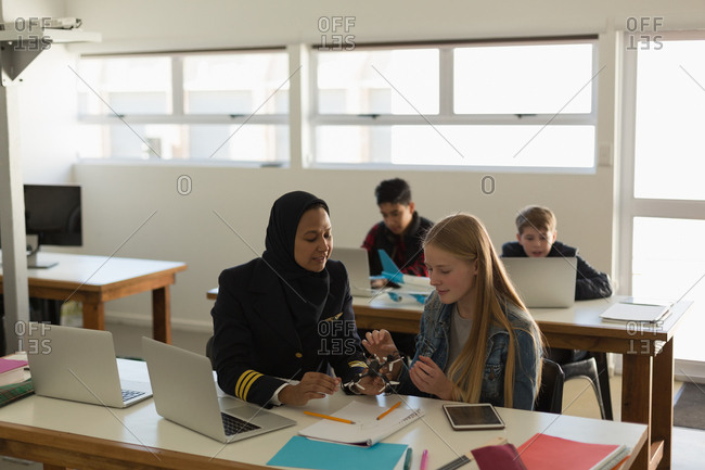Female pilot teaching about model drone to student in training institute