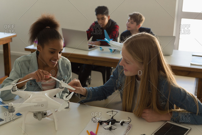 Students discussing together over model airplane in training institute