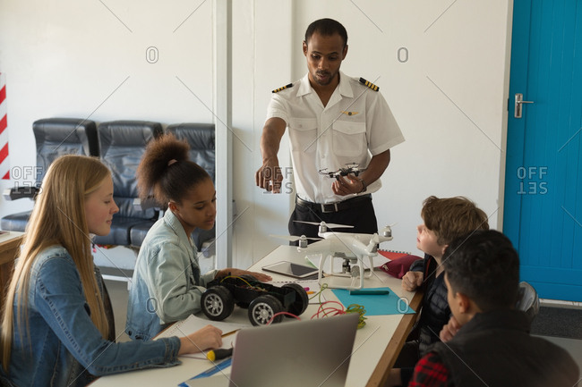 Pilot giving training about model airplane to students in the training institute