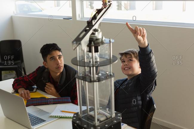 Attentive kids discussing over machine in the training institute