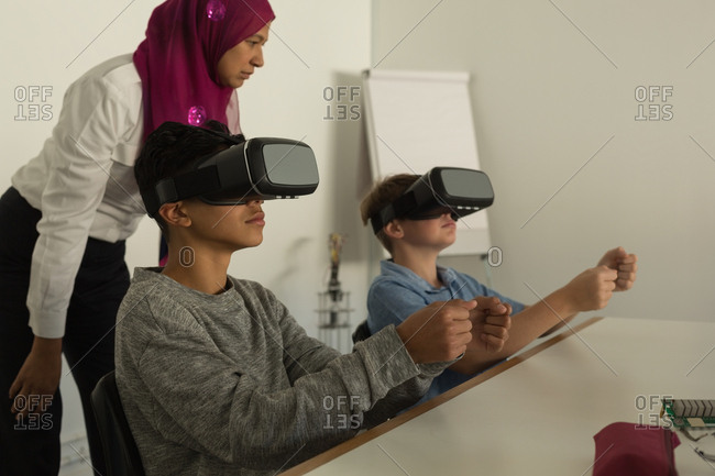 Female pilot giving training on virtual reality headset to students in training institute
