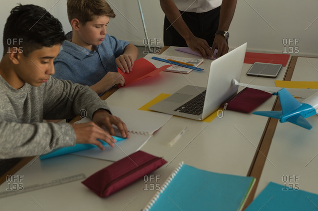 Kids making paper plane with craft paper in training institute