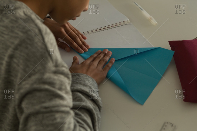 Close-up of kid making paper plane with craft paper in training institute