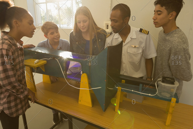 Male pilot explaining about machine to kids in training institute