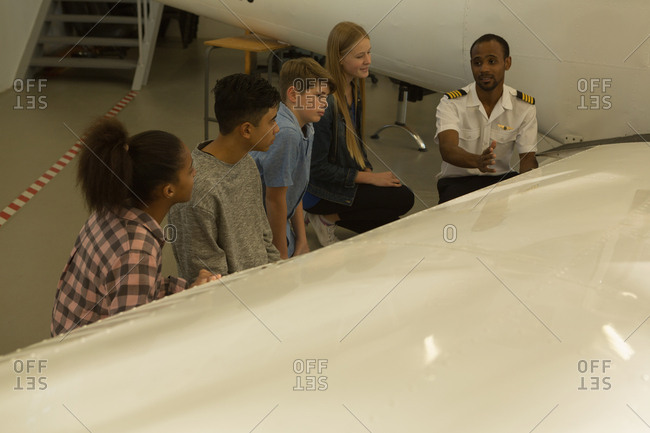 Male pilot explaining about airplane to kids in training institute