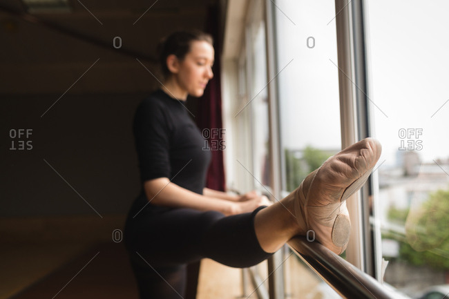 Ballerina stretching on barre while practicing ballet dance in dance studio
