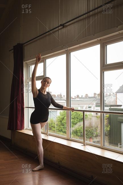 Ballerina practice arabesque ballet position in dance studio