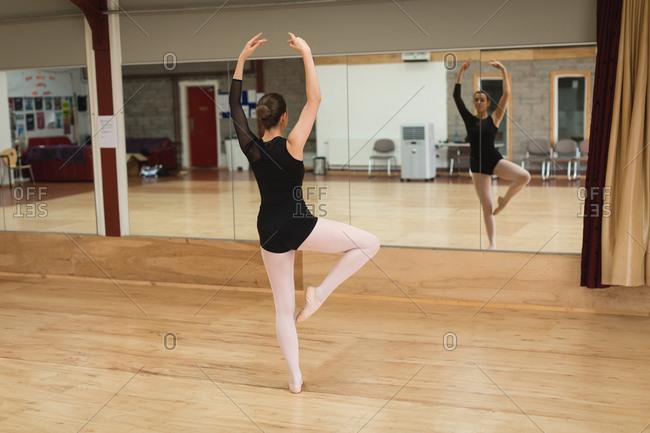 Ballerina dancing in front of mirror in dance studio