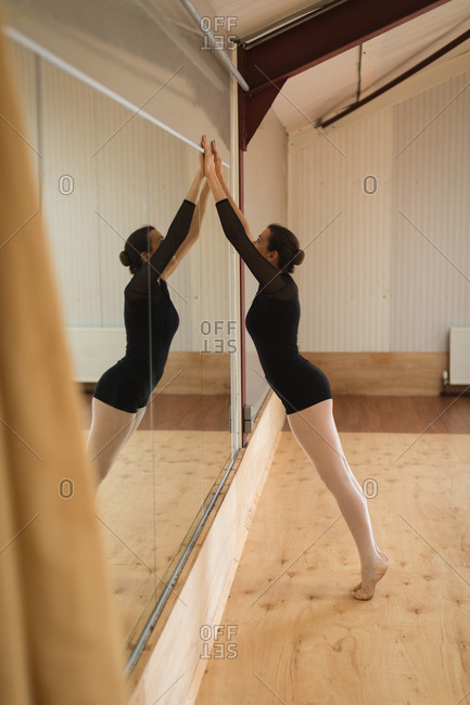 Side view of ballerina stretching in front of mirror in studio