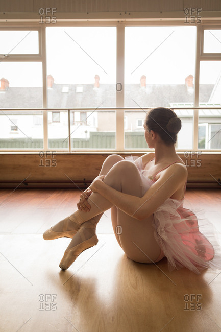Thoughtful ballerina looking through window while sitting on wooden floor in dance studio