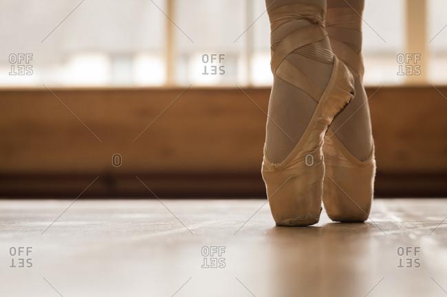 Low section of ballerina dancing on wooden floor in dance studio