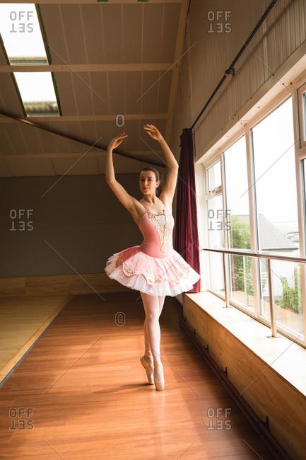 Beautiful ballerina practicing ballet dance in dance studio