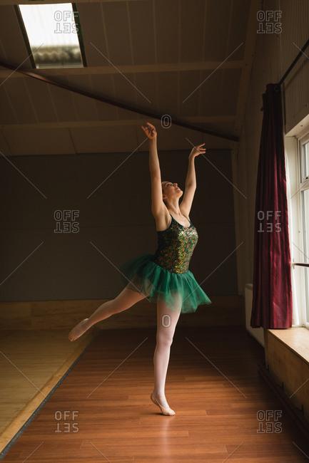 Beautiful ballerina practice arabesque ballet position in dance studio
