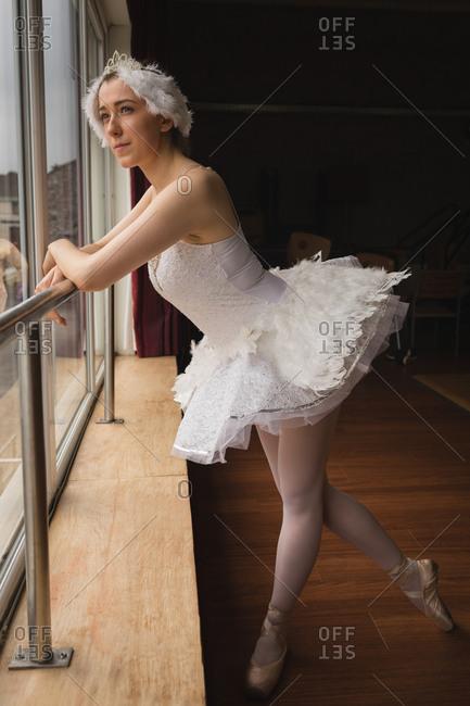 Thoughtful ballerina looking through window in dance studio