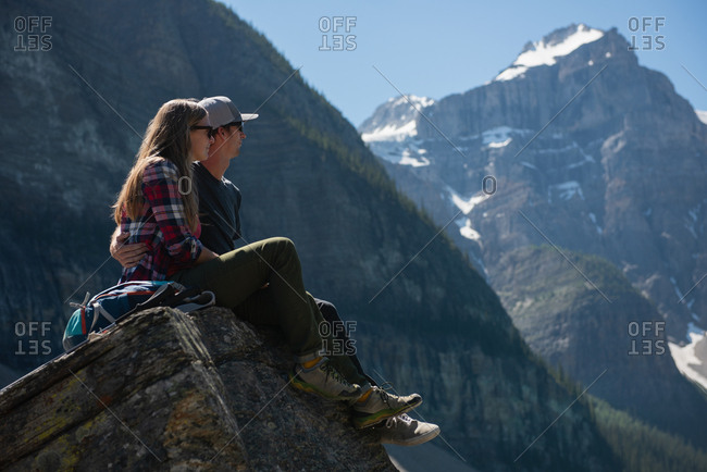 Romantic couple sitting on a rock near mountain