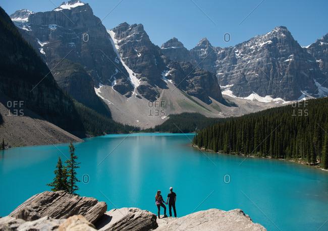 Rear view of couple standing on rock near riverside