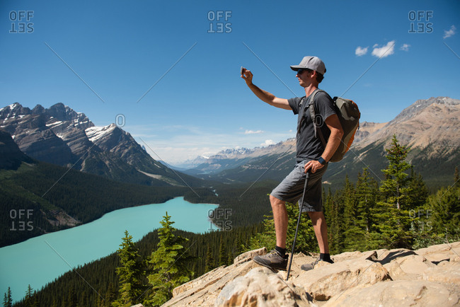 Man clicking pictures with mobile phone while standing on a rock at countryside