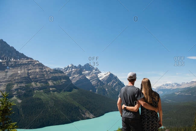 Rear view of couple standing with arm around in countryside