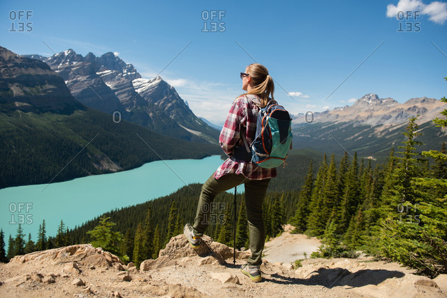 Female hiker standing with backpack at countryside on a sunny day